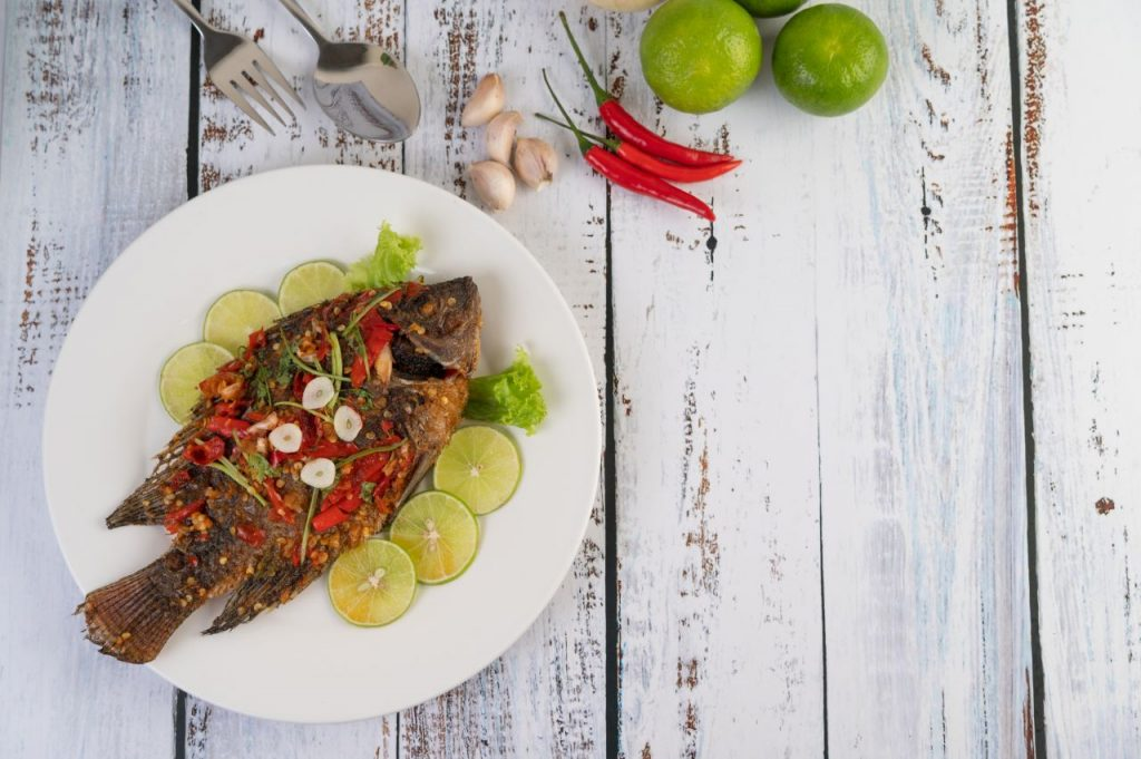 Fried Tilapia With Chili Sauce Lemon Salad Garlic Plate White Wooden Background (1)